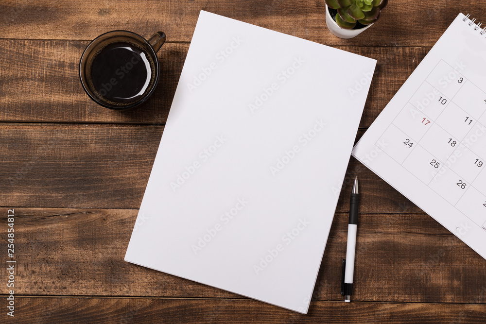 Fototapeta top view image of open notebook with blank pages next to cup of coffee on wooden table. ready for adding text or mockup.