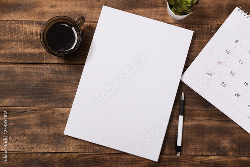 Fotografía top view image of open notebook with blank pages next to cup of coffee on wooden table