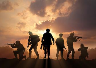 Sześć wojskowych sylwetek na tle nieba słońca