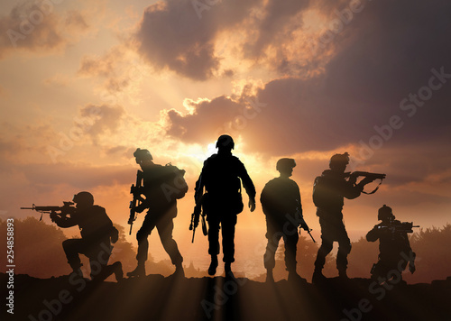 Fotografía  Six military silhouettes on sunset sky background