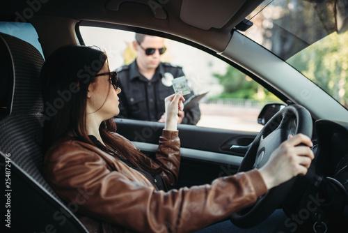 Obraz Male cop in uniform writes a fine to female driver - fototapety do salonu