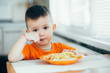 beautiful baby in orange t-shirt with orange plate eating fried French fries