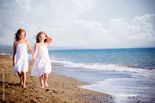 belle bambine a camminare sulla riva del mare Wallpaper Mural