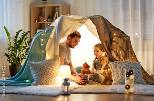 Obraz family, hygge and people concept - happy father with teddy bear toy and little daughter playing in kids tent at night at home - fototapety do salonu