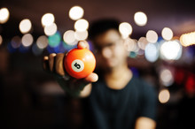 Orange Pool Ball With 5 Hold At Hands Man. Blured Background. Billiard Theme.