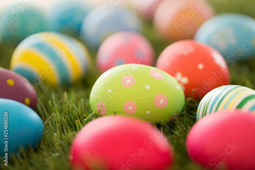 easter, holidays and tradition concept - colored eggs on artificial grass