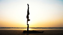 Silhouette Of Fit Sporty Couple Practicing Acrobatic Yoga With Partner Together On The Sandy Beach. Female Acrobat Doing Handstand On The Hands Of His Lying Male Partner.