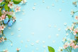Beautiful spring nature background with butterfly, lovely blossom, petal a on turquoise blue background , top view, frame. Springtime concept.