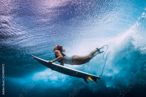 Photographie Surfer woman dive underwater. Surfgirl dive under big wave