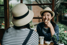 Two Asian Woman Travelers In Hats Sitting In Japanese Style Old Wooden House Experience Culture Of Sado. Happy Girl Friends Chatting Laughing While Eating Sweet Snacks Drinking Matcha Green Tea Teien