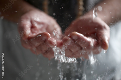 Valokuva  Muslim man washes his hands before prayer ritual cleansing.