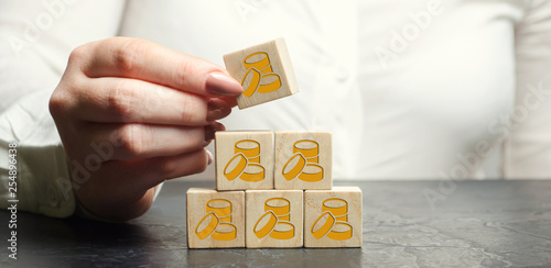 Businesswoman puts or removes wooden blocks with coins Canvas Print