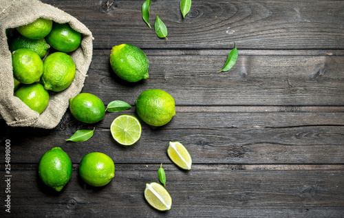 Fotografering Fresh lime in the sack and pieces of juicy lime.