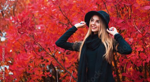 Fasonuje jesień portreta uśmiechniętej kobiety w czarnym kapeluszu na czerwonym liścia tle