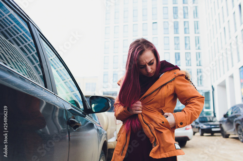 Fototapeta  Pretty young woman standing and looking keys of car in her bag outdoors