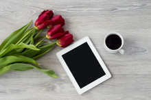 White Tablet With A Cup Of Coffee And Red Flowers Lies On A White Wooden Table.