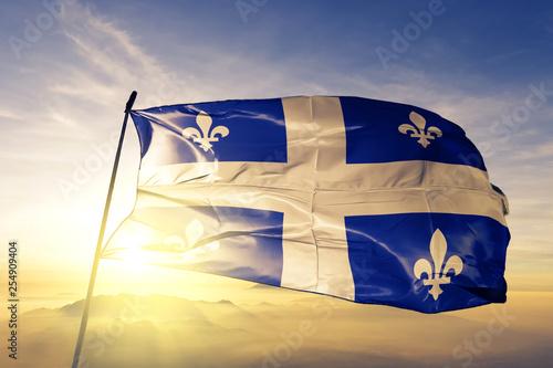 Fototapeta premium Flaga prowincji kanadyjskiej prowincji Quebec macha na szczycie mgły o wschodzie słońca