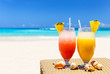 canvas print picture - Two tropical fresh juices on white sandy beach