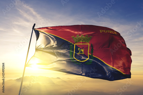 Fotografía Ponce municipality of Puerto Rico flag waving on the top sunrise mist fog