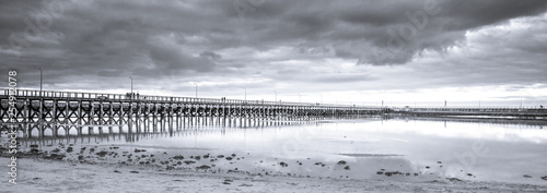 Aluminium Prints Dark grey Wooden pier, clouds and stormy sky reflected in calm waters of North Sea - seaside landscape of Northumberland
