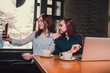 Two female students or lesbians having fun during coffee break at cafe, second half distract from work.