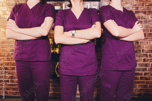 Portrait of female brunette cosmetologist in uniform in the cosmetology office three young women Fototapete