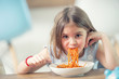 Cute little kid girl eating spaghetti bolognese at home