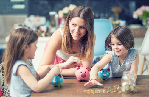 Fototapeta Happy Family mom daughter save money piggy bank future investment savings obraz