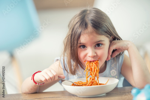 Fototapeta Cute little kid girl eating spaghetti bolognese at home obraz