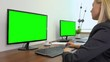 An office worker sits at a desk and works on a computer with a green screen - another desk with a green screen computer in the background