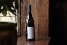 Bottle Of Red Wine On Wooden Background. Blank Label For Your Text Or Logo. Mock Up