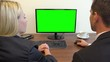 Two office workers, man and woman, sit at a desk and talk, the man works on a computer with a green screen - closeup