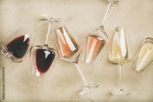 Flat-lay of red, rose and white wine in glasses over grey concrete background, top view. Wine bar, winery, wine degustation concept