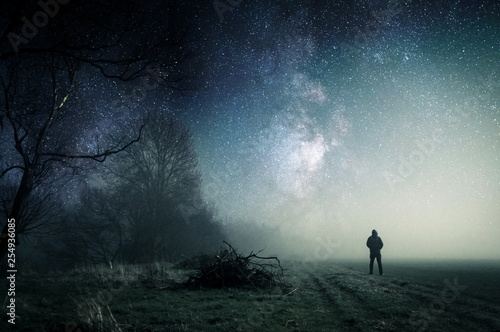 A lone hooded figure standing on a path on a spooky misty night, with a cold blue edit.