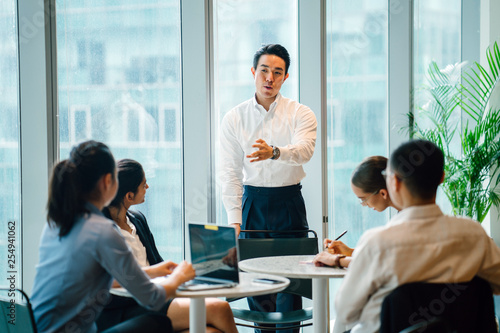 A gorgeous, sure, and fit Asian Chinese man seats a gathering with his group amid the day in the workplace Fototapet