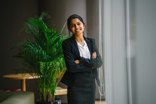 Image Of A Modern Asian Indian Businesswoman Standing By A Glass Window Ledge In The Office. She Laughs And Strikes A Glamorous Pose Before The Camera.
