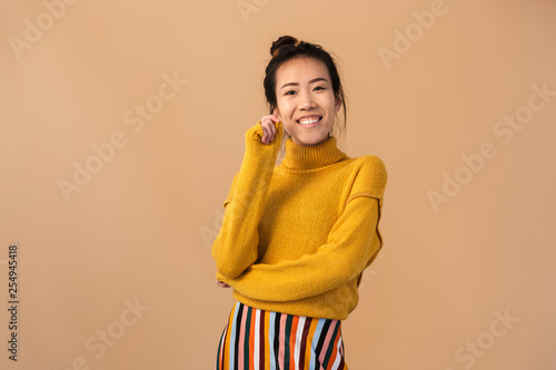 Fotografia  Image of gorgeous japanese woman wearing sweater smiling and looking at camera