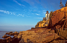 Bass Harbor Head Lighthouse Catches First Rays Of Sunrise Above Rocky Shore On Mt. Desert Island, Maine