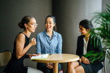 Three Professional Women Of Different Ethnic Backgrounds Are Sitting Down And Having A Meeting Around A Table In A Meeting Room During The Day. All Of Them Are Professionally And Competently Dressed.