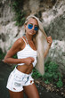beautiful woman with long blonde hair in blue glasses, white shirt and denim shorts posing on backgraund of rocks in Bali