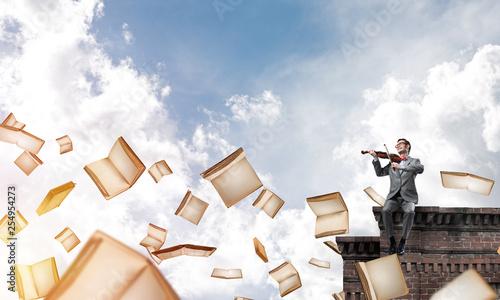 Przystojny skrzypek gra swoją melodię i latające książki