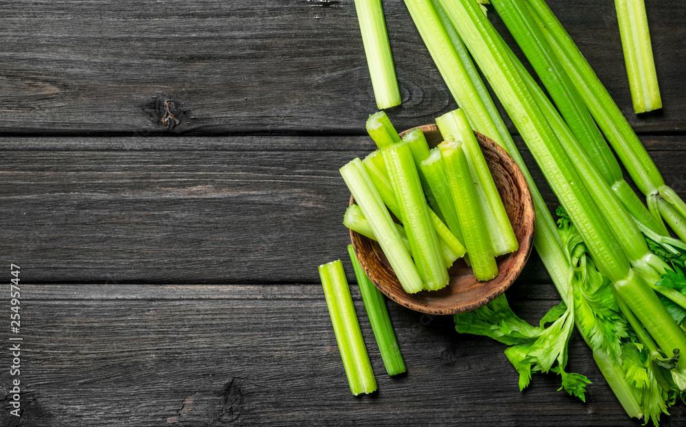 Fototapeta Pieces of celery in a wooden bowl.