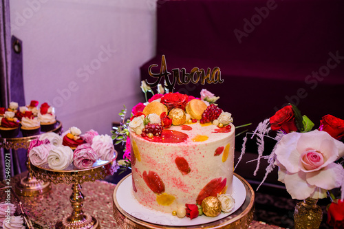 Photo Beautiful cake decorated of candies and roses with the inscription Alena