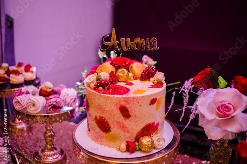 Photo The cake decorated of candies and roses with the inscription Alena