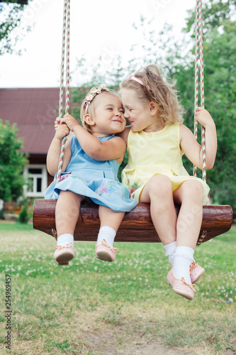 Fotografiet  Two cheerful little caucasian blondie girls outdoors on swing in countryside