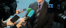 Interview, Report, Media. Abstract Man In A Suit And Tie Speaks To Reporters And Video Cameras. Female Hands Hold Microphones, Voice Recorders And Mobile Phones To Record Sound.