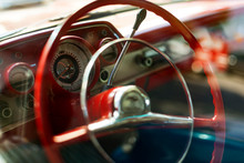 Steering Wheel View Of A Red Colored 1957 Chevrolet.