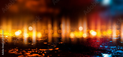Fotografia  Wet asphalt, reflection of neon lights, a searchlight, smoke