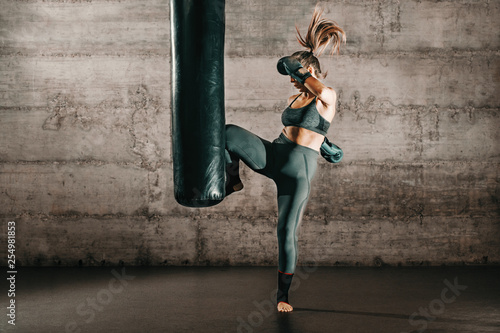 Fotografía  Dedicated strong brunette with ponytail, in sportswear, bare foot and with boxing gloves kicking sack in gym