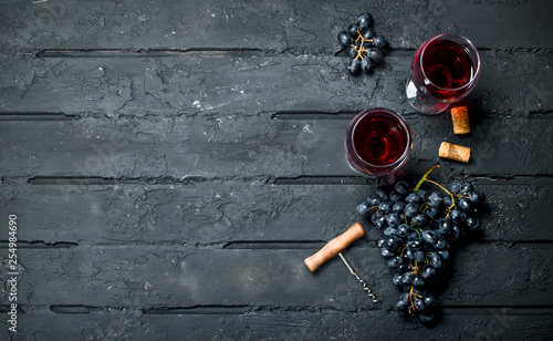 Foto auf Leinwand Alkohol Wine background. Red wine with grapes and corkscrew.